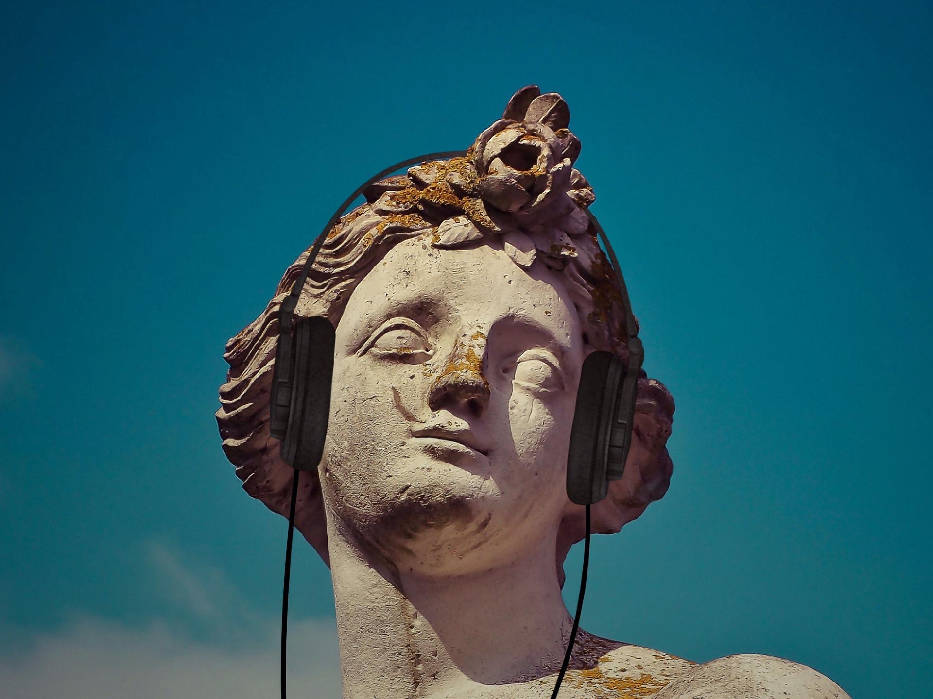 Kuvassa kreikkalaistyylinen kulunut patsas, jonka päässä on modernit kuulokkeet.