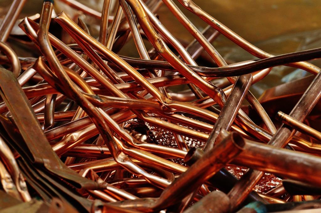 kuvassa on läheltä kuvattu kasa kuparin värisiä metalliputkia, jotka ovat taittuneet eri kohdista